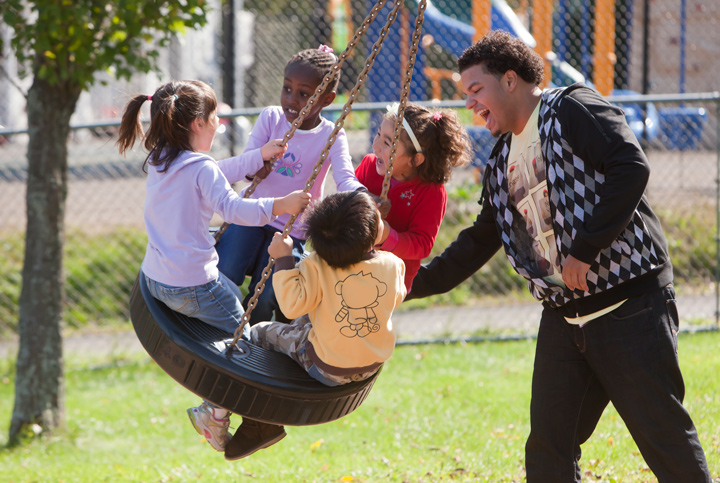 Young adult playing with children on playground